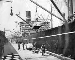 Workers loading sacks of flour by crane onto the vessel SS <i>Africa Maru</i>, ca. 1926. Item number: PA096.002.